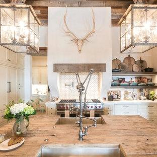 オースティンの巨大なカントリー風おしゃれなキッチン (エプロンフロントシンク、シェーカースタイル扉のキャビネット、ベージュのキャビネット、木材カウンター、茶色いキッチンカウンター、白いキッチンパネル、テラコッタタイルのキッチンパネル、パネルと同色の調理設備、無垢フローリング、茶色い床) の写真