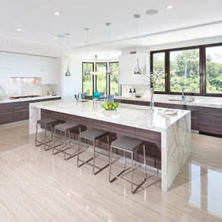 Open concept kitchen - huge contemporary u-shaped porcelain tile open concept kitchen idea in Los Angeles with flat-panel cabinets, dark wood cabinets, white backsplash, stone slab backsplash, an island, a single-bowl sink and marble countertops