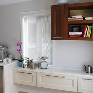 Inspiration for a mid-sized contemporary galley light wood floor eat-in kitchen remodel in Montreal with an undermount sink, recessed-panel cabinets, white cabinets, solid surface countertops, multicolored backsplash, mosaic tile backsplash, stainless steel appliances and an island