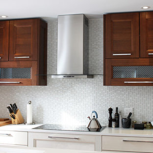 Mid-sized trendy galley light wood floor kitchen photo in Montreal with an undermount sink, flat-panel cabinets, white cabinets, solid surface countertops, gray backsplash, mosaic tile backsplash, stainless steel appliances and an island