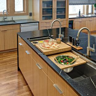 ミネアポリスの中サイズのコンテンポラリースタイルのおしゃれなキッチン (アンダーカウンターシンク、フラットパネル扉のキャビネット、中間色木目調キャビネット、ソープストーンカウンター、緑のキッチンパネル、ガラス板のキッチンパネル、シルバーの調理設備の、無垢フローリング、オレンジの床、緑のキッチンカウンター) の写真