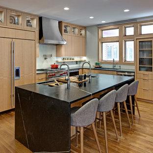 他の地域の中くらいのコンテンポラリースタイルのおしゃれなキッチン (アンダーカウンターシンク、フラットパネル扉のキャビネット、中間色木目調キャビネット、ソープストーンカウンター、緑のキッチンパネル、ガラス板のキッチンパネル、シルバーの調理設備、無垢フローリング、オレンジの床、緑のキッチンカウンター) の写真