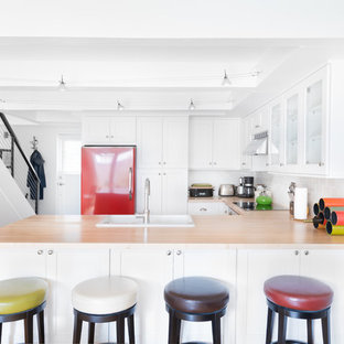 Photo of a small transitional u-shaped kitchen in Seattle with shaker cabinets, white cabinets, wood benchtops, white splashback, ceramic splashback, medium hardwood floors, a peninsula, a drop-in sink, coloured appliances and brown floor.