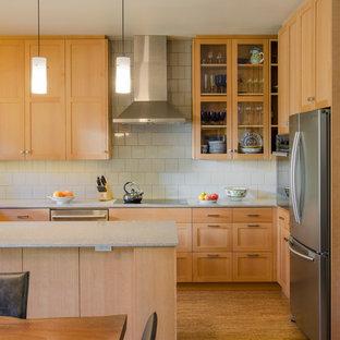 Diseño de cocina contemporánea con armarios con paneles empotrados, puertas de armario de madera clara, salpicadero blanco, salpicadero de azulejos de cerámica, electrodomésticos de acero inoxidable, una isla y suelo de corcho
