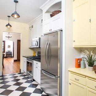 Ispirazione per una cucina classica con ante in stile shaker, ante gialle, paraspruzzi bianco, elettrodomestici in acciaio inossidabile, pavimento multicolore e top giallo