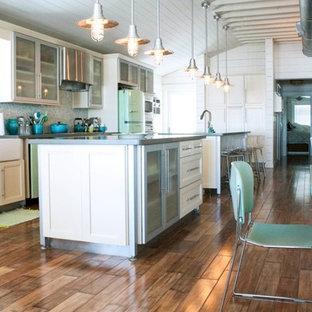 Foto di una cucina stile marinaro con lavello stile country, ante di vetro, ante bianche, top in cemento, paraspruzzi multicolore, paraspruzzi con piastrelle di vetro, elettrodomestici colorati e pavimento in legno massello medio
