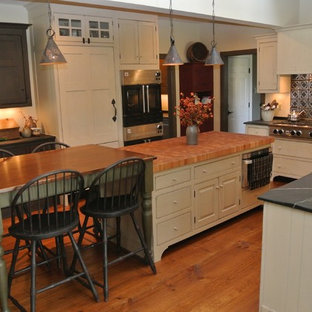 This is an example of a large farmhouse l-shaped open plan kitchen in New York with a belfast sink, recessed-panel cabinets, beige cabinets, soapstone worktops, black splashback, stainless steel appliances, medium hardwood flooring and an island.
