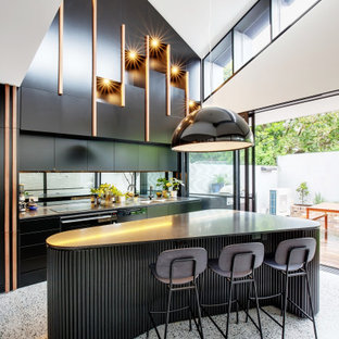 Mid-sized contemporary single-wall open plan kitchen in Other with a double-bowl sink, flat-panel cabinets, black cabinets, metallic splashback, mirror splashback, terrazzo floors, with island and multi-coloured floor.