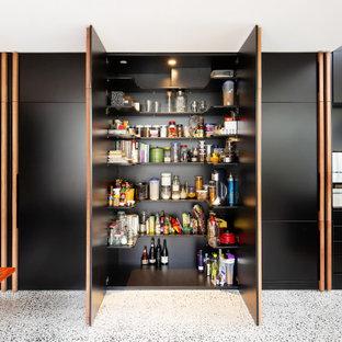 Ispirazione per una cucina lineare minimal di medie dimensioni con lavello da incasso, ante in stile shaker, ante nere, top in quarzo composito, paraspruzzi nero, paraspruzzi a specchio, elettrodomestici neri, pavimento alla veneziana, isola, pavimento grigio e top nero