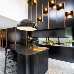Modern inredning av ett mellanstort svart linjärt svart kök, med en nedsänkt diskho, skåp i shakerstil, svarta skåp, bänkskiva i kvarts, svart stänkskydd, spegel som stänkskydd, svarta vitvaror, terrazzogolv, en köksö och grått golv