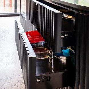 Einzeilige, Mittelgroße Moderne Küche mit Einbauwaschbecken, Schrankfronten im Shaker-Stil, schwarzen Schränken, Quarzwerkstein-Arbeitsplatte, Küchenrückwand in Schwarz, Rückwand aus Spiegelfliesen, schwarzen Elektrogeräten, Terrazzo-Boden, Kücheninsel, grauem Boden und schwarzer Arbeitsplatte in Sonstige