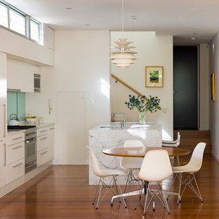 Modern inredning av ett kök, med en undermonterad diskho, vita skåp, marmorbänkskiva, glaspanel som stänkskydd, rostfria vitvaror, en köksö, brunt golv, släta luckor, blått stänkskydd och mörkt trägolv