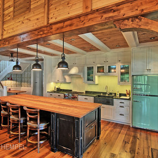 Large rustic galley open plan kitchen in Minneapolis with a belfast sink, shaker cabinets, distressed cabinets, granite worktops, green splashback, coloured appliances, medium hardwood flooring and an island.