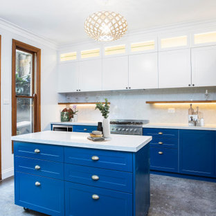 Photo of a mid-sized beach style l-shaped eat-in kitchen in Sydney with a drop-in sink, shaker cabinets, blue cabinets, quartz benchtops, white splashback, stone slab splashback, stainless steel appliances, concrete floors, with island, grey floor and white benchtop.