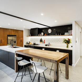 シドニーの巨大なインダストリアルスタイルのおしゃれなキッチン (ダブルシンク、中間色木目調キャビネット、大理石カウンター、白いキッチンパネル、セラミックタイルのキッチンパネル、シルバーの調理設備の、コンクリートの床) の写真