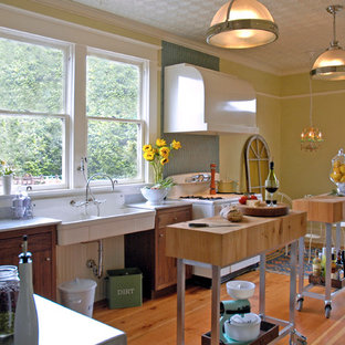 Small traditional single-wall separate kitchen in Portland with a farmhouse sink, marble benchtops, flat-panel cabinets, dark wood cabinets, blue splashback, glass tile splashback, white appliances, multiple islands and medium hardwood floors.