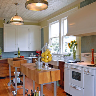 Inspiration for a mid-sized cottage l-shaped enclosed kitchen remodel in Portland with a farmhouse sink, marble countertops, blue backsplash, white appliances, glass tile backsplash, shaker cabinets, white cabinets and two islands