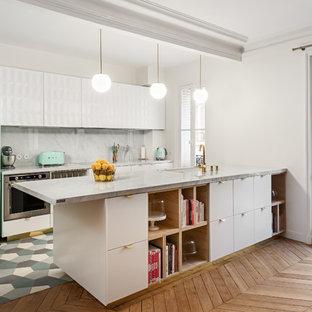 エセックスの中サイズのエクレクティックスタイルのおしゃれなキッチン (エプロンフロントシンク、フラットパネル扉のキャビネット、白いキャビネット、大理石カウンター、グレーのキッチンパネル、大理石の床、シルバーの調理設備の、無垢フローリング、茶色い床) の写真