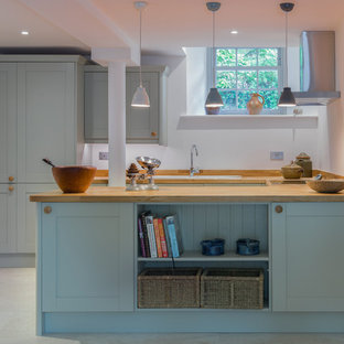 Small traditional u-shaped kitchen in Devon with a submerged sink, recessed-panel cabinets, grey cabinets, wood worktops, no island, grey floors and beige worktops.