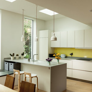 Contemporary galley kitchen in London with a submerged sink, flat-panel cabinets, white cabinets, yellow splashback, medium hardwood flooring, an island, brown floors and grey worktops.