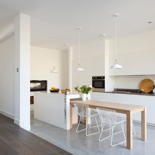 Design ideas for a mid-sized contemporary single-wall eat-in kitchen in London with a drop-in sink, flat-panel cabinets, white cabinets, subway tile splashback, stainless steel appliances, concrete floors, with island and multi-coloured floor.