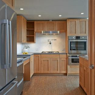 シアトルの中サイズのトランジショナルスタイルのおしゃれなキッチン (シェーカースタイル扉のキャビネット、淡色木目調キャビネット、白いキッチンパネル、サブウェイタイルのキッチンパネル、シルバーの調理設備の、竹フローリング、ダブルシンク、人工大理石カウンター、茶色い床) の写真