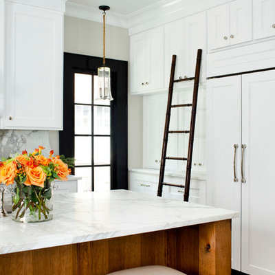Inspiration for a mid-sized timeless l-shaped medium tone wood floor enclosed kitchen remodel in Atlanta with marble countertops, an undermount sink, recessed-panel cabinets, white cabinets, white backsplash, paneled appliances and an island