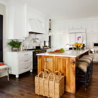 Enclosed kitchen - mid-sized traditional l-shaped medium tone wood floor enclosed kitchen idea in Atlanta with recessed-panel cabinets, white cabinets, white backsplash, stone slab backsplash, black appliances, marble countertops, an undermount sink and an island