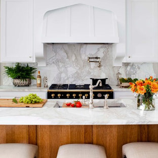 Mid-sized traditional l-shaped kitchen in Atlanta with an undermount sink, marble benchtops, white splashback, panelled appliances, recessed-panel cabinets, white cabinets, medium hardwood floors, with island and marble splashback.