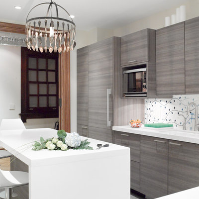 Eat-in kitchen - mid-sized transitional l-shaped eat-in kitchen idea in New York with an undermount sink, flat-panel cabinets, gray cabinets, paneled appliances, quartz countertops, multicolored backsplash and an island