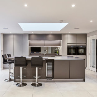 Design ideas for a medium sized contemporary single-wall open plan kitchen in Other with flat-panel cabinets, grey cabinets, mirror splashback, black appliances, an island, an integrated sink, quartz worktops, metallic splashback, porcelain flooring, grey floors, grey worktops and a vaulted ceiling.