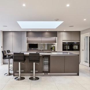 Inredning av ett modernt mellanstort grå linjärt grått kök med öppen planlösning, med släta luckor, grå skåp, spegel som stänkskydd, svarta vitvaror, en köksö, en integrerad diskho, bänkskiva i kvartsit, stänkskydd med metallisk yta, klinkergolv i porslin och grått golv