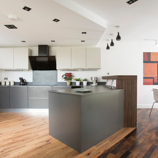 Photo of a contemporary u-shaped kitchen/diner in Other with flat-panel cabinets, grey cabinets, laminate countertops, grey splashback, stainless steel appliances, medium hardwood flooring, a breakfast bar, brown floors and grey worktops.