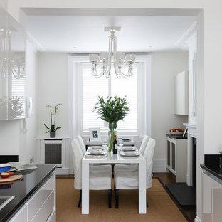 Exemple d'une cuisine américaine chic avec un évier encastré, un placard à porte plane, des portes de placard grises, une crédence grise et une crédence en feuille de verre.