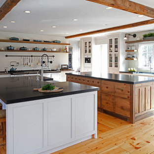 ニューヨークの大きいカントリー風おしゃれなキッチン (エプロンフロントシンク、シェーカースタイル扉のキャビネット、御影石カウンター、無垢フローリング、白いキャビネット、白い調理設備、茶色い床) の写真