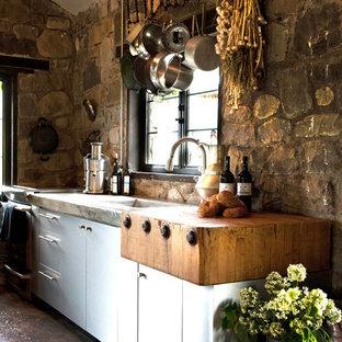 Foto de cocina lineal, rústica, pequeña, abierta, con fregadero integrado, armarios con paneles lisos, puertas de armario en acero inoxidable, encimera de cemento, suelo de cemento, una isla, salpicadero beige y electrodomésticos de acero inoxidable
