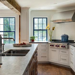 Foto di una grande cucina classica con lavello sottopiano, ante in stile shaker, ante bianche, paraspruzzi bianco, paraspruzzi in legno, elettrodomestici in acciaio inossidabile, pavimento in legno massello medio, isola, pavimento marrone e top in granito