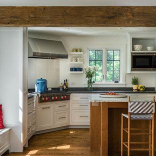 ブリッジポートの広いエクレクティックスタイルのおしゃれなキッチン (アンダーカウンターシンク、シェーカースタイル扉のキャビネット、白いキャビネット、白いキッチンパネル、木材のキッチンパネル、シルバーの調理設備、無垢フローリング、茶色い床、御影石カウンター) の写真