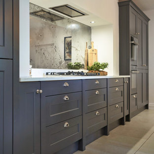 Inspiration for a mid-sized traditional galley eat-in kitchen in Belfast with a farmhouse sink, shaker cabinets, grey cabinets, quartzite benchtops, metallic splashback, glass sheet splashback, black appliances, ceramic floors, with island, beige floor and yellow benchtop.