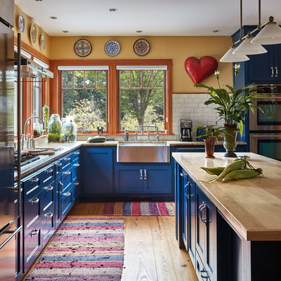 Example of a country l-shaped medium tone wood floor and brown floor kitchen design in Bridgeport with a farmhouse sink, shaker cabinets, blue cabinets, wood countertops, white backsplash, subway tile backsplash, stainless steel appliances, an island and brown countertops