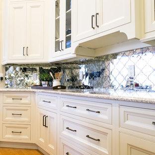 Foto di una cucina tradizionale di medie dimensioni con lavello sottopiano, ante con riquadro incassato, ante bianche, top in granito, paraspruzzi a specchio, elettrodomestici neri, parquet chiaro, isola e pavimento marrone