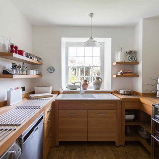 Small contemporary u-shaped enclosed kitchen in London with medium wood cabinets, stainless steel appliances, medium hardwood flooring, brown floors, a built-in sink, flat-panel cabinets, wood worktops, white splashback and no island.