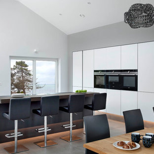 Contemporary l-shaped kitchen/diner in Belfast with flat-panel cabinets, white cabinets, black appliances, cement flooring, an island and grey floors.