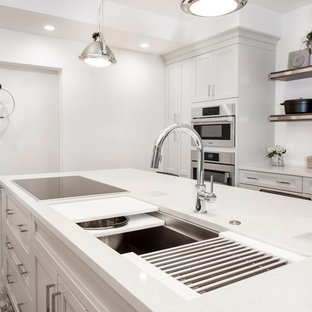 This is an example of a mid-sized transitional single-wall eat-in kitchen in Other with an undermount sink, quartzite benchtops, white splashback, stainless steel appliances, vinyl floors, with island, brown floor, shaker cabinets, grey cabinets and porcelain splashback.
