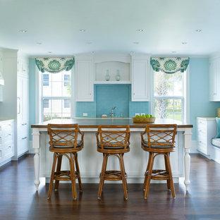 Foto di una cucina stile marinaro di medie dimensioni con ante in stile shaker, ante bianche, paraspruzzi blu, paraspruzzi con piastrelle diamantate, parquet scuro, isola, lavello sottopiano, top in legno e elettrodomestici in acciaio inossidabile