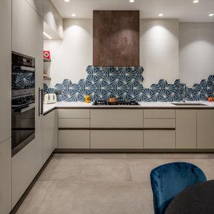 ロンドンの大きいエクレクティックスタイルのおしゃれなキッチン (シングルシンク、フラットパネル扉のキャビネット、グレーのキャビネット、大理石カウンター、青いキッチンパネル、セメントタイルのキッチンパネル、シルバーの調理設備、セラミックタイルの床、アイランドなし、グレーの床、白いキッチンカウンター) の写真
