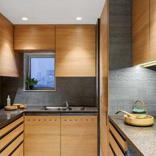 Moderne Küche in U-Form mit Unterbauwaschbecken, flächenbündigen Schrankfronten, hellen Holzschränken, Küchenrückwand in Grau, buntem Boden und brauner Arbeitsplatte in Mumbai