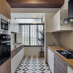 Zweizeilige, Große Moderne Küche ohne Insel mit Unterbauwaschbecken, flächenbündigen Schrankfronten, weißen Schränken, Arbeitsplatte aus Holz, bunter Rückwand, Elektrogeräten mit Frontblende, Porzellan-Bodenfliesen, buntem Boden und brauner Arbeitsplatte in Bangalore
