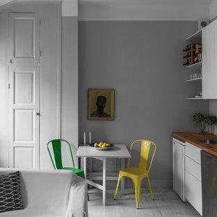 Diseño de cocina lineal, nórdica, pequeña, abierta, sin isla, con fregadero encastrado, armarios con paneles lisos, puertas de armario blancas, encimera de madera, electrodomésticos de acero inoxidable y suelo de madera pintada