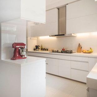 シンガポールの中サイズのモダンスタイルのおしゃれなキッチン (ダブルシンク、白いキャビネット、クオーツストーンカウンター、白いキッチンパネル、ガラス板のキッチンパネル、シルバーの調理設備の、セラミックタイルの床、アイランドなし) の写真